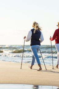 Nordic walking - active people working on beach