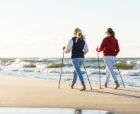 Nordic walking - active people working on beach